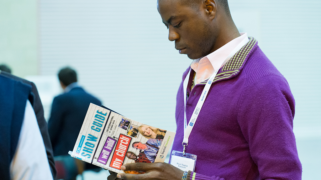 Photo of a CRE visitor looking at the CRE show guide