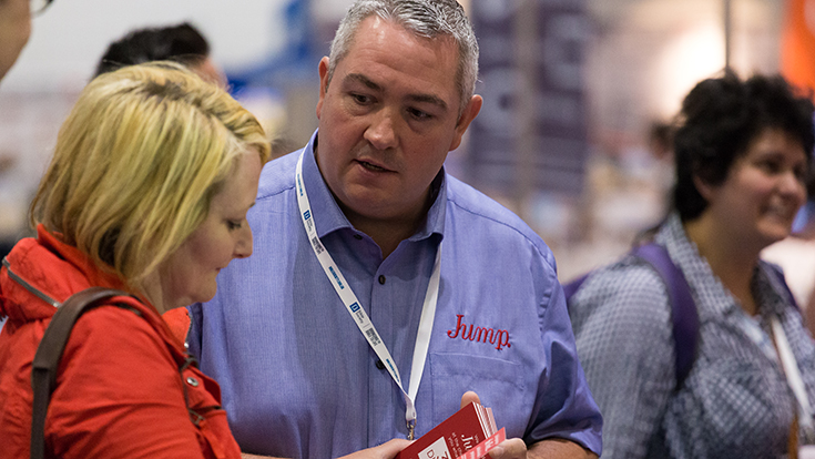 Photo of an exhibitor talking with a visitor at CRE