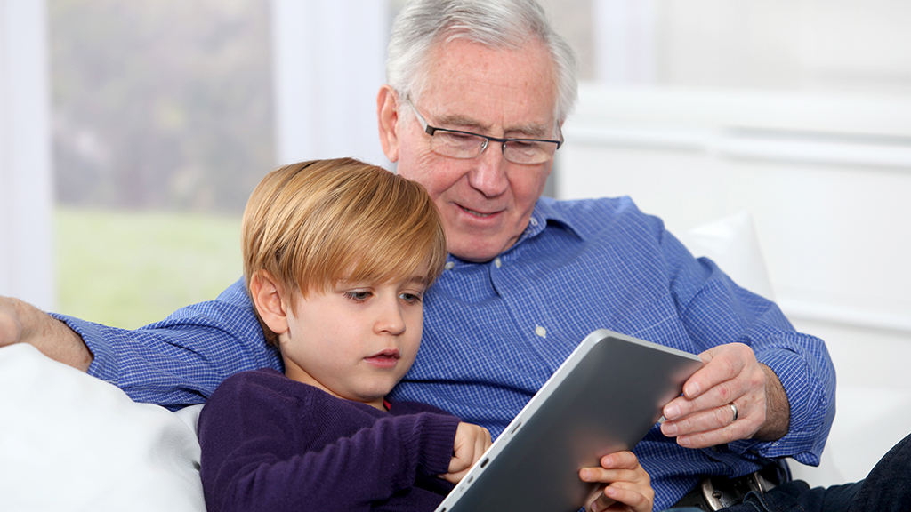 Grandfather and grandson using a tablet
